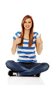 Happy teenage woman sitting with cross legged and showing OK sign