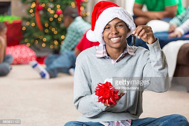 Happy teenager gets keys to a car for Christmas