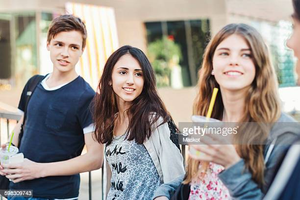 Happy teenagers looking at friend outdoors