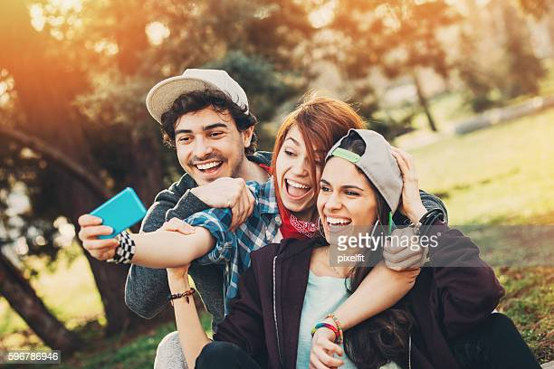 Happy teenagers making selfie in the park