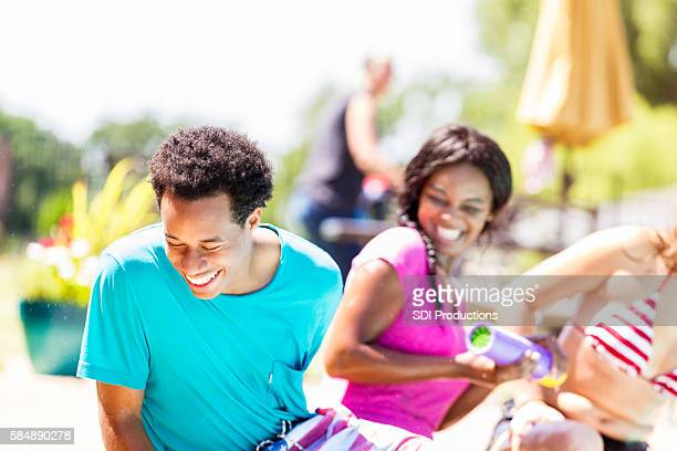 Happy teens laughing and playing together by the pool