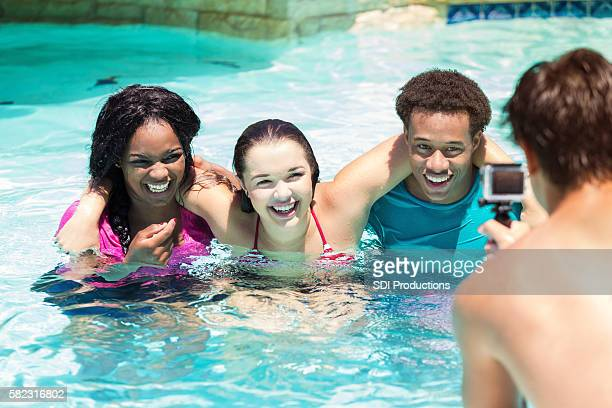 Happy teens laughing together in the pool with wearable camera