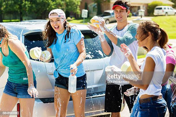 Happy teens playing and splashing around at a car wash