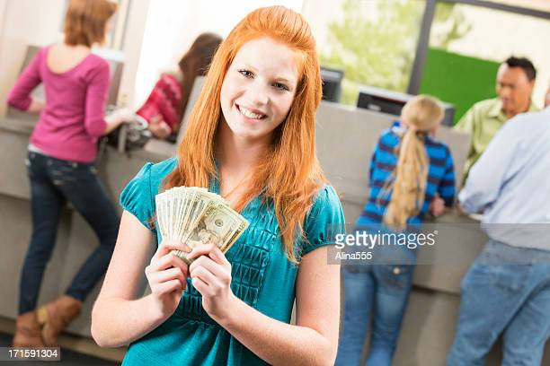 Happy tenager with money at the bank branch