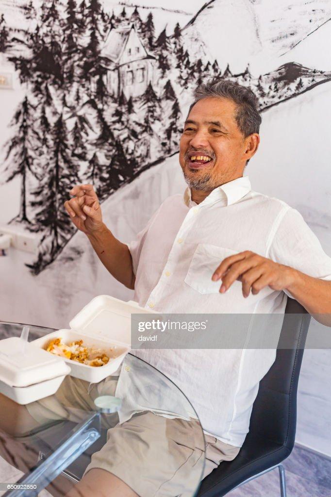 Gelukkig Thaise Senior Man lachen terwijl het eten van voedsel meenemen : Stockfoto