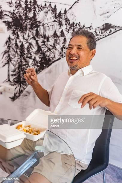 Happy Thai Senior Man Laughing While Eating Take Away Food