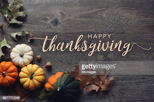 Happy Thanksgiving greeting text with pumpkins, squash and leaves over dark wood background : Stock Photo