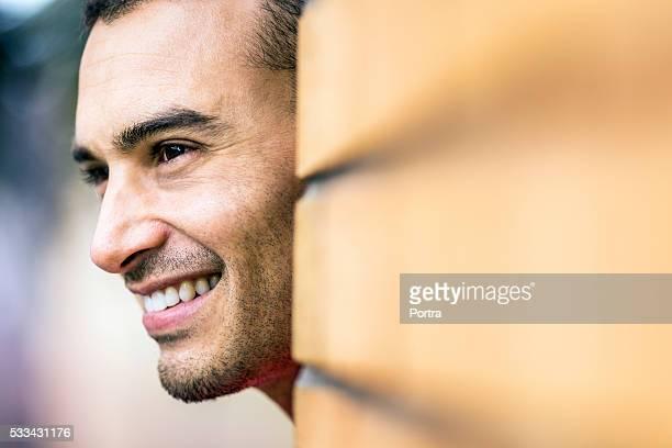 Heureux homme pensif par mur de briques