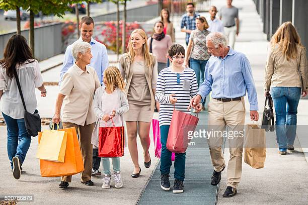 Glückliche Familie mit drei Generationen mit Einkaufstüten zu Fuß