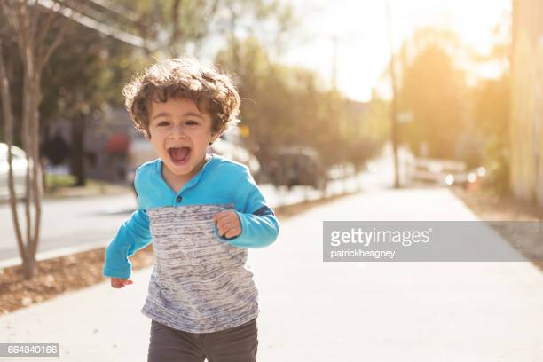 Happy Toddler Boy Running Down the Sidewalk