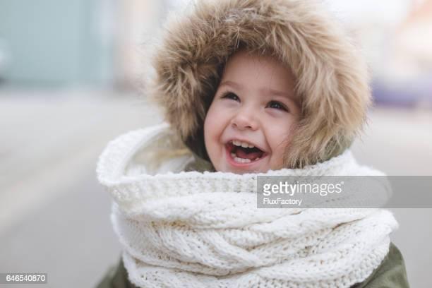 Happy toddler girl laughing - winter fashion