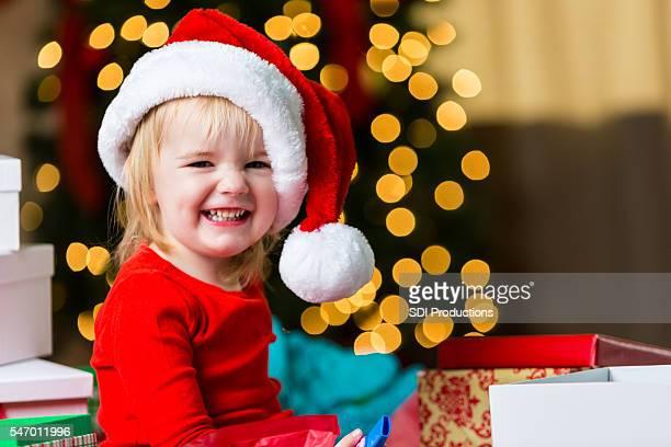 Happy toddler girl wearing santa hat at Christmas