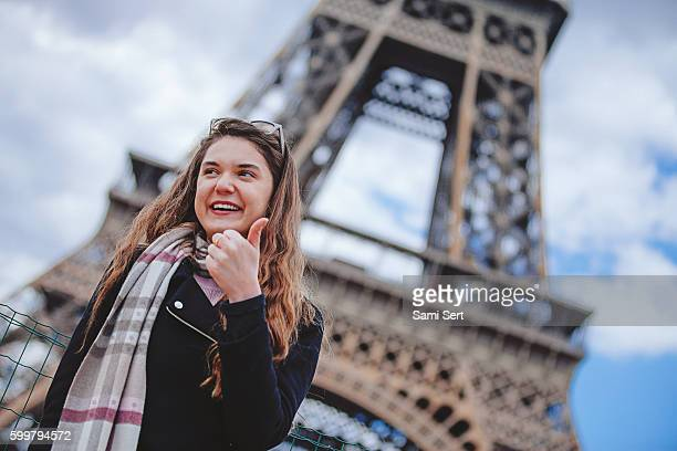 Happy tourist woman showing thumbs up in Paris