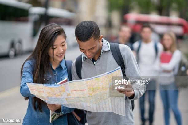 Happy tourists sightseeing in London and holding a map
