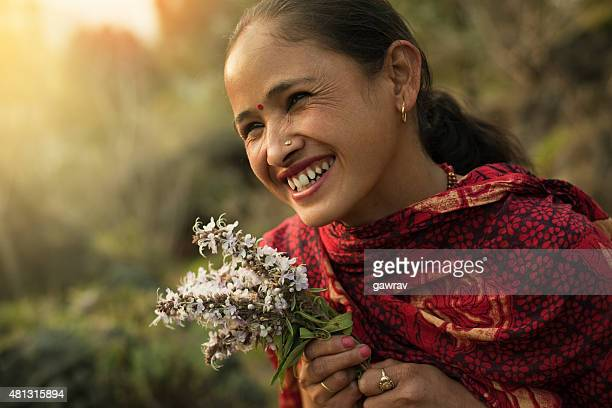 Happy traditional Asian woman looking away in rural nature.