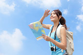 Happy travel woman look map and look copy space with sky background, asian