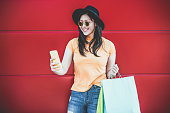 Happy trendy asian girl using shopping app holding bags outdoor - Young woman having fun buying new clothes on web with smartphone - Retail, tech, sales and buyer addiction concept - Focus on face