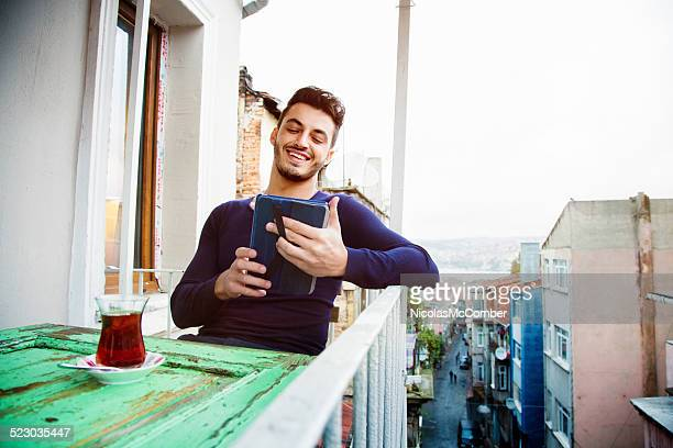 Happy Turkish man using digital tablet on his balcony