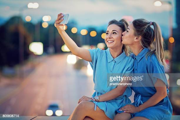 Happy twin sisters are taking selfie/video call