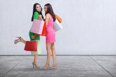 Happy two asian woman with shopping bags standing against white wall background