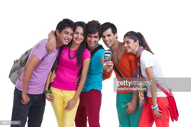 Happy university friends taking picture of themselves on white background