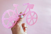 Lady on city bike concept. Minimal style pink bike over pink background, copy space