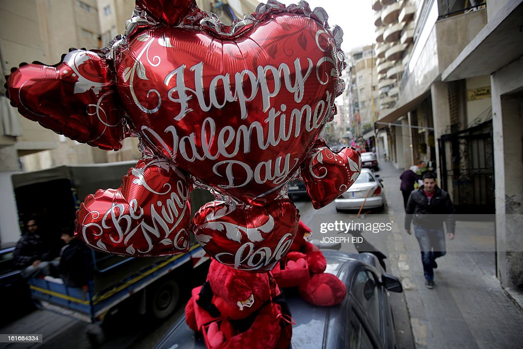 Happy Valentine's Day ballons hang on top of a car parked in the mainly Muslim Basta district of west Beirut on February 14, 2013. Valentine's Day is increasingly popular in the region as people have taken up the custom of giving flowers, cards, chocolates and gifts to sweethearts to celebrate the occasion. AFP PHOTO/JOSEPH EID