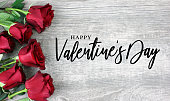 Happy Valentine's Day Calligraphy with Red Roses Over Rustic Wood Background