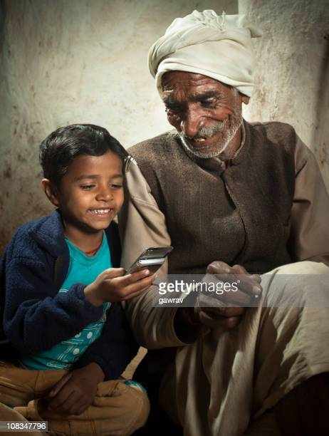Happy village boy playing with his grandfather's mobile phone