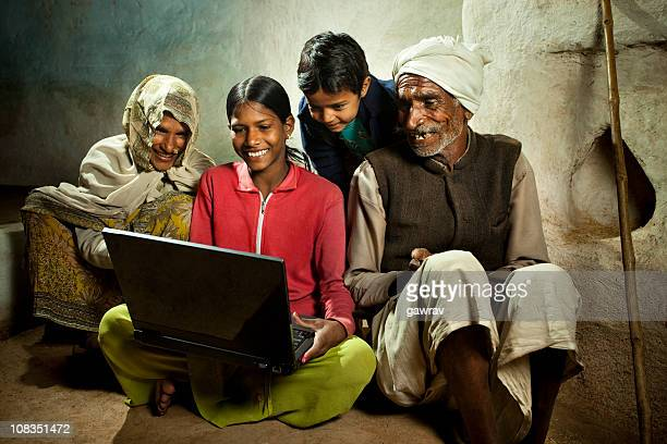 Happy village girl using laptop with mother, brother and grandfa