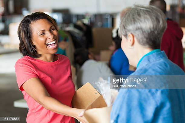 Happy volunteer accepting donations at food and clothing bank