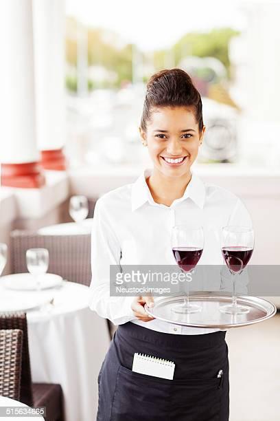 Glücklich Kellnerin tragen Teller mit Weingläser im Restaurant