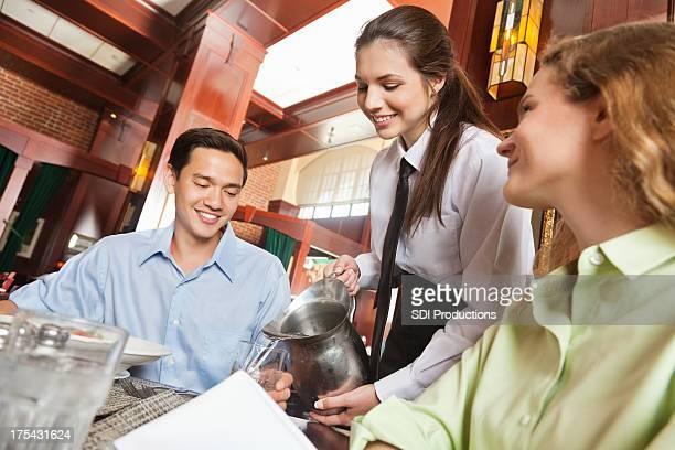 Happy waitress refilling drinks in nice restaurant