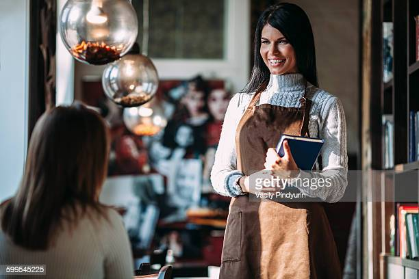 Happy waitress talking to female customer in coffee shop