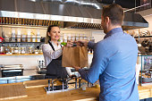 Happy waitress waring apron serving customer at counter in small family eatery restaurant. Small business and entrepreneur concept with woman owner in eatery with takeaway service delivery