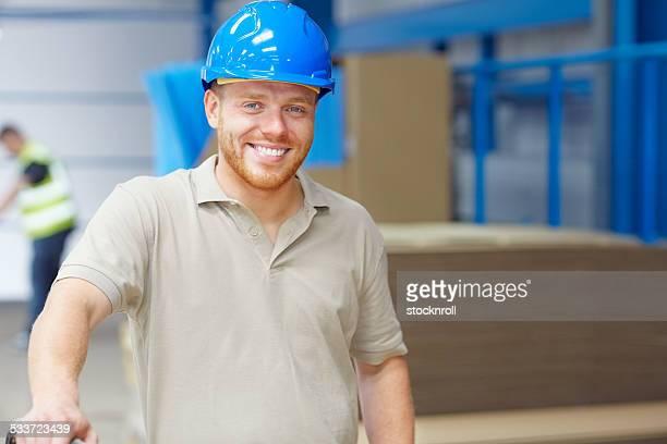 Happy warehouse worker wearing a hardhat