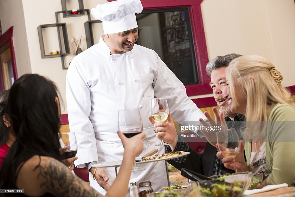 Happy welcoming chef with customers in a restaurant : Stock Photo