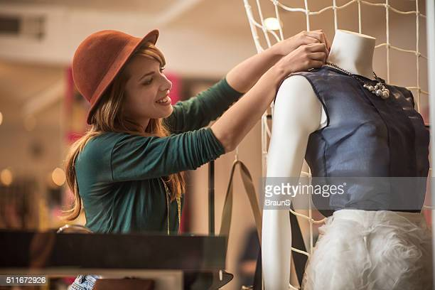 Happy woman adjusting blouse on a mannequin in a store.