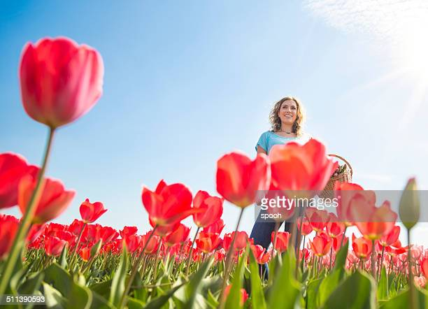 Happy woman among red tulips