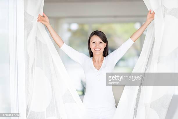 Glückliche Frau zu Hause Öffnen der Fenster
