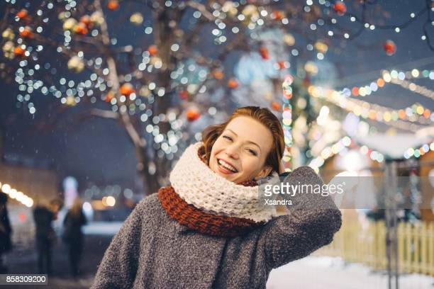 Femme heureuse au marché de Noël dans la nuit