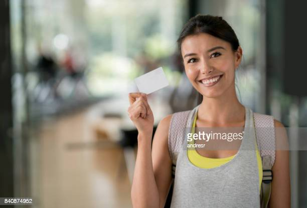 Happy woman at the gym holding a loyalty card
