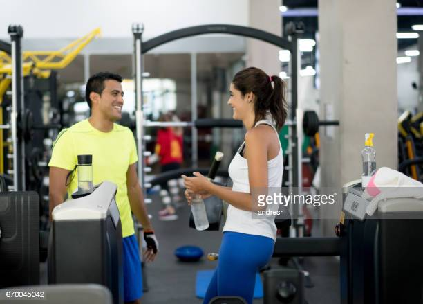 Happy woman at the gym talking to her personal trainer