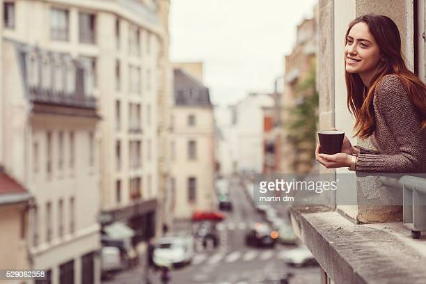 Happy woman at the window with a cup of coffee