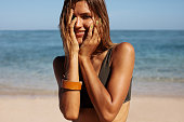 Close up portrait of smiling female standing outdoors on the beach with her hands on face. Happy woman bikini model on sea shore.