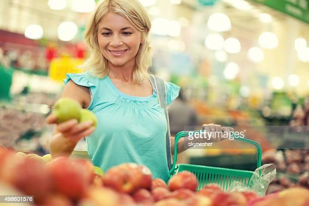 Happy woman buying fruits at farmer's market.