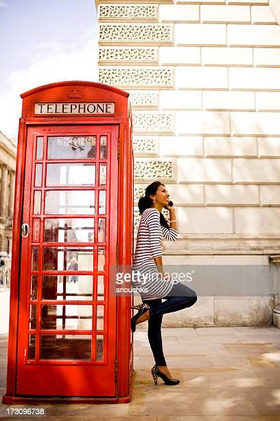 Happy Woman Calling From Traditional London Phone Booth