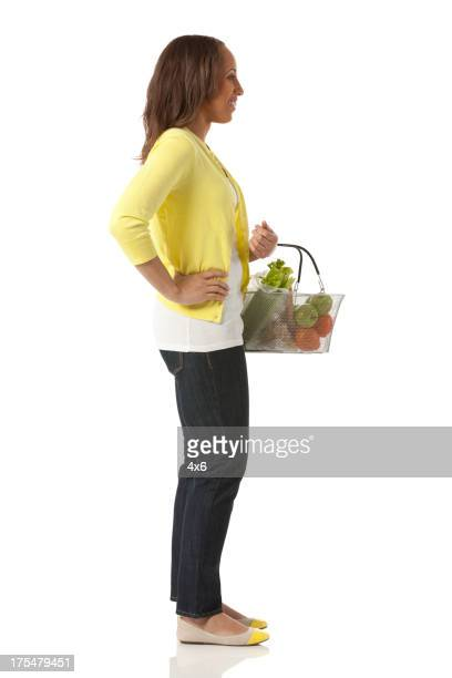 Happy woman carrying a basket of fruits