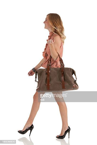 Donna felice portando con sé una borsa a mano
