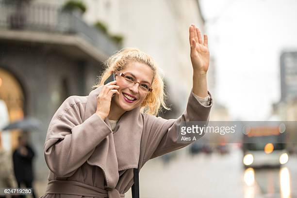 Happy woman catching a taxi